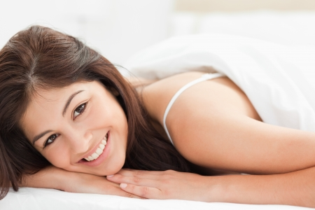 head tilted forward: A close up shot of a woman lying on a bed with her head, resting on her hands, tilted to the side looking forward and smiling.
