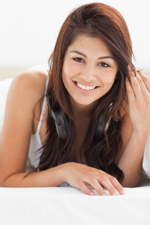 A close up shot of a smiling woman with her fingers in her hair as she looks forward. Stock Photo - 13672284