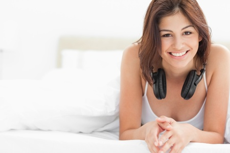 A woman at the end of the bed with headphones around her neck, she is smiling while looking forward.  photo