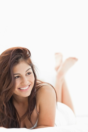 A close up shot of a woman with a smile and crossed legs while looking to the side. photo