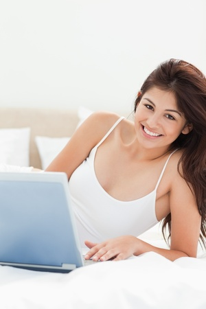 A woman is using her laptop while she looks ahead and smiles, all while relaxing on the bed. Stock Photo - 13650487
