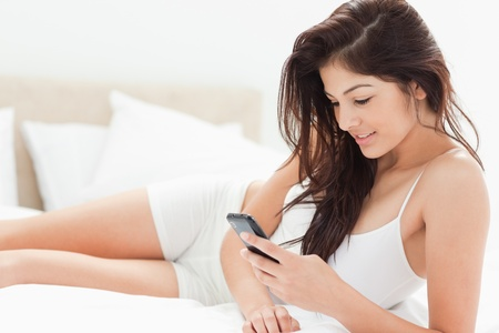A woman using her smartphone as she lies down the legth of the bed and smiling. photo