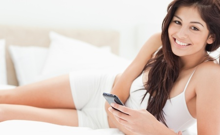 A woman looking up from her smartphone and smiling as she relaxs on the bottom of her bed. photo