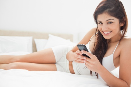 A woman lying down the length of her bed as she smiles and interacts with her smartphone. photo