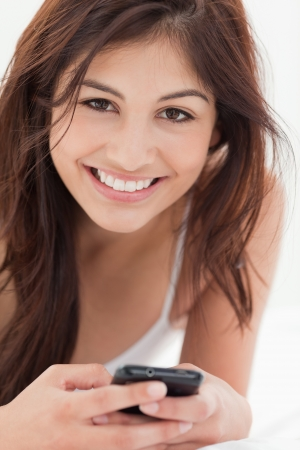 A close up shot of a woman smiling as she holds her smartphone. photo