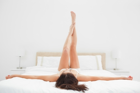 stretched out: A woman lying on her back, with her legs raised straight up while her arms are stretched out fully across the bed.
