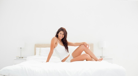 A wide angle shot, showing a woman sitting across the width of the bed, with a knee raised, smiling. it also shows the entire room. Stock Photo - 13648645