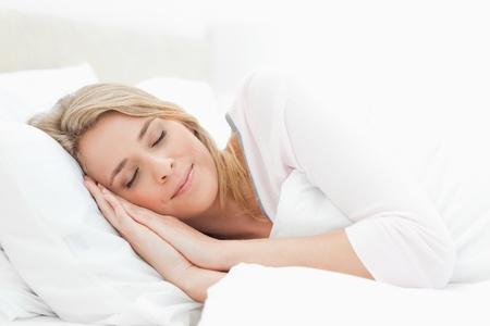 durmiendo: Una mujer durmiendo en la cama, la cabeza apoyada en una almohada con las manos junto a su cabeza. Y una colcha que cubre hasta el hombro. Foto de archivo