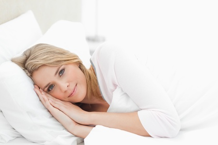 A horizontal view shot of a woman resting in bed, eyes open with her hands and head both resting on the pillow. photo