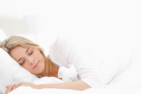 gente durmiendo: Una mujer que duerme con los brazos extendidos un poco fuera delante de ella.