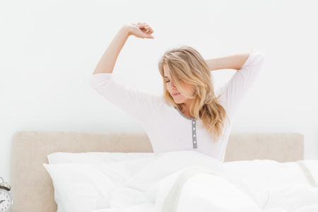 strecthing: A woman upright in bed, one arm strecthing and the other behind her head which is turned to the side. Stock Photo