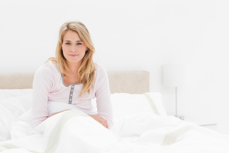 just ahead: A woman is sitting up in bed, with a quilt over her waist, her arms just in front of her as she smiles and looks straight ahead.