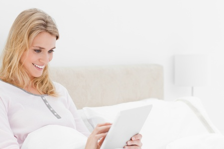 A closer shot of a woman sitting in bed watching tablet pc and smiling. Stock Photo - 13650249