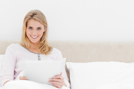A woman is holding a tablet pc and smiling as she sits upright in bed. Stock Photo - 13650201