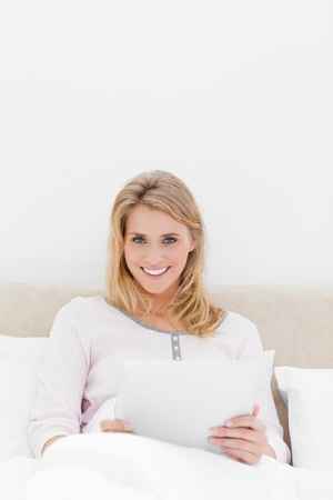 A centered shot of a woman with a tablet pc, looking forward and smiling while in bed. Stock Photo - 13649935