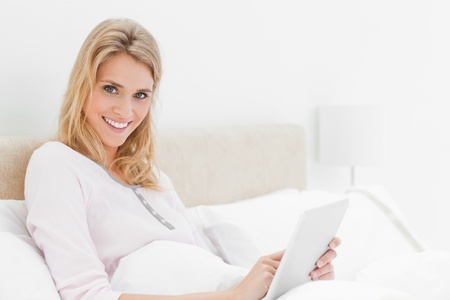 A woman sitting in bed using her tablet pc, while looking up and to the side while smiling. Stock Photo - 13650211