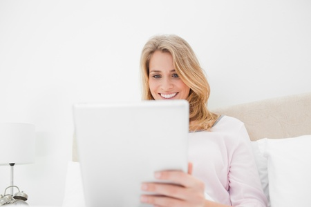 A low angle shot of a woman using a tablet pc and smiling while in bed. Stock Photo - 13650093