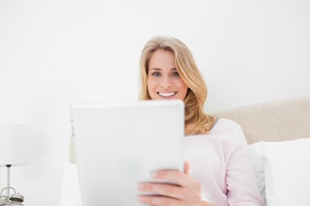 A low angle shot of a woman in bed with a tablet pc in hand as she is looking forward and smiling. Stock Photo - 13650170