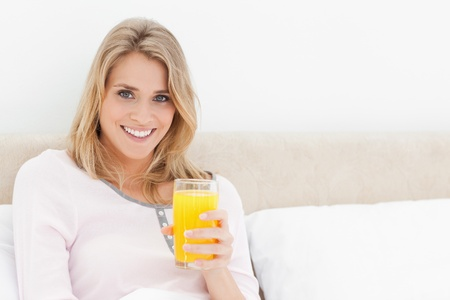 A woman sitting in bed with a glass of orange juice while she is looking forward and smiling. photo
