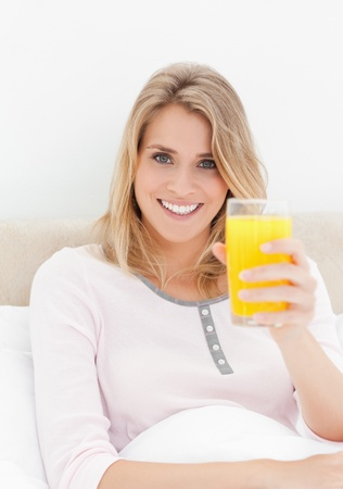 A close up shot of a woman smiling and looking forward while holding a raised glass of orange juice. photo