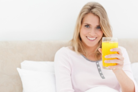 A woman holding a glass of orange juice while smiling and looking forward, while in bed. photo