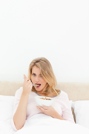 A vertical shot of a woman about to eat a spoon of cereal, looking forward while in bed. Stock Photo - 13650005
