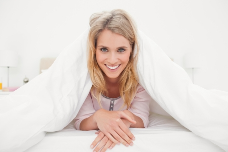 wider: A wider view of a woman smiling while lying down the bed under the quilt with her hands crossed.