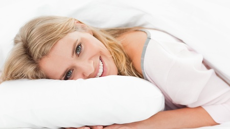 A woman lying in bed with her hands under a pillow and head on it, with her eyes open and smiling. photo