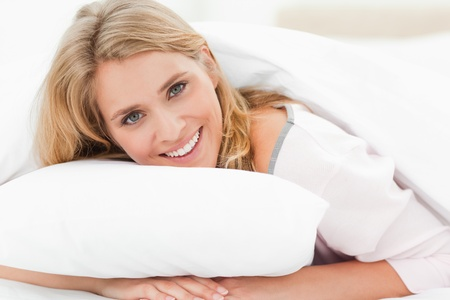A woman lying in bed, with her head raised from the pillow slightly, smiling as her hands are under the pillow. Stock Photo - 13651047