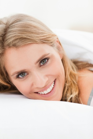 A close up shot of a woman lying in bed smiling, with her head slightly raised but still on the pillow. photo