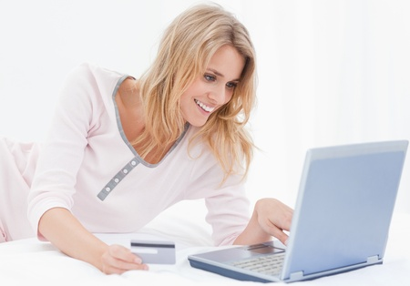order online: A smiling woman lying on her bed, using her laptop and credit card to order items online.