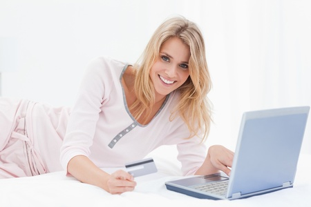 A woman is lying on the bed smiling as she looks forward while ordering items online with her laptop and credit card photo