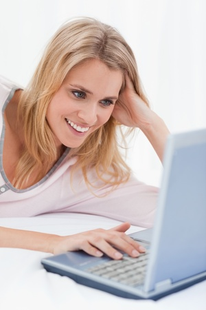 A close up shot of a woman using her laptop and smiling while lying on the bed. photo