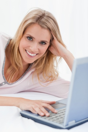A close up shot of a woman lying on her bed, with her laptop beside her. Stock Photo - 13659137