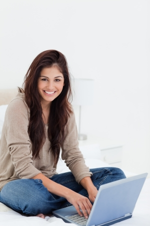 A woman sits on her bed with her laptop as she looks to the side smiling, with her legs crossed. photo