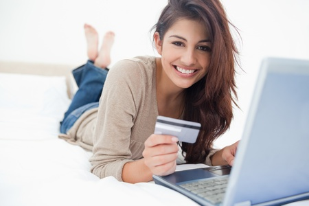 credit cards: A woman smiling and looking in front of her as she uses her credit card with her laptop. Stock Photo