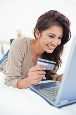 A close up shot of a woman smiling with a credit card in hand and laptop in front of her. photo
