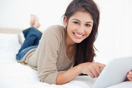 A woman lies on her bed as she smiles using her tablet and looking in front of her. photo