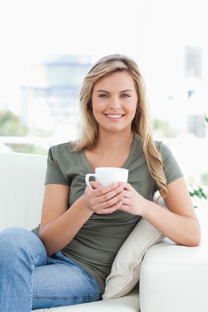 A woman sitting on the couch with crossed legs, a cup in her hands and smiling. Stock Photo - 13672281
