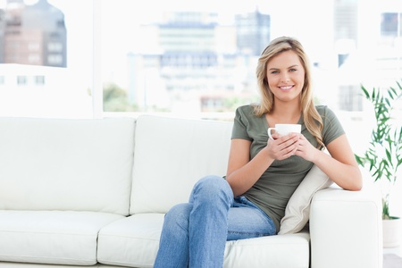 A woman sitting at the side of the couch, with a cup in her hands, a smile and looking forward. photo