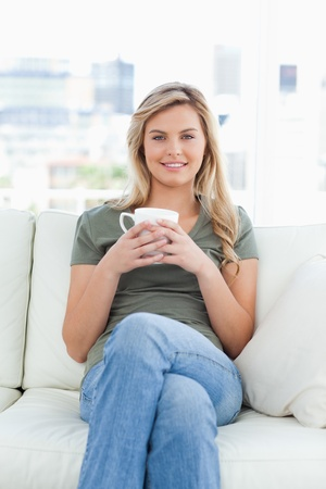 centered: A centered shot, woman smiling and sitting on the couch with her legs crossed and holding a cup in her hands. Stock Photo
