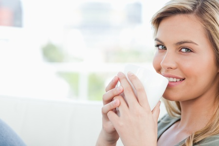 women holding cup: A woman holding a cup to her lips while smiling and looking in front of her. Stock Photo