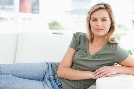 lies forward: A woman with her arms on the arm rest, looking forward as she lies across the couch.