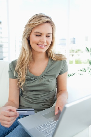 A smiling woman looking at her laptop while holding her credit card and sitting on the couch. Stock Photo - 13657796