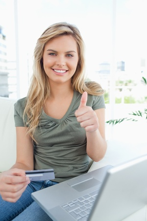 A woman with credit card in hand and laptop beside her, smiles giving a thumbs up. photo