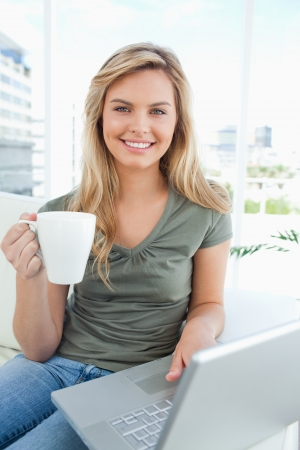 A woman smiles as she uses her laptop and holds a cup in her hand, all while looking in front of her. photo