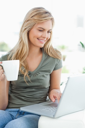A woman sitting on the couch, smiling as she uses her laptop and hold a cup in her hand photo