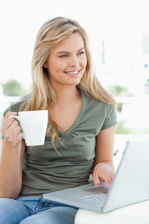 A woman looking slightly sideways, as she uses her laptop and holds a cup, while sitting on the couch. photo