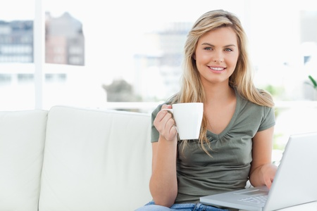A woman sitting on the couch, smiles as she looks in front of her, a cup in her hand and using her laptop. photo