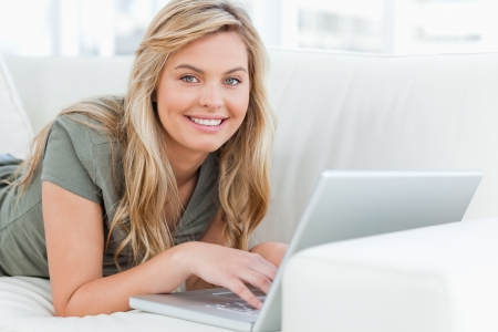 lies forward: A woman using her laptop as she lies across the couch, smiling and looking forward.